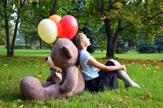 Smutna dziewczynka z dużym misiem i balony w parku. problemy nastolatków w szkole.