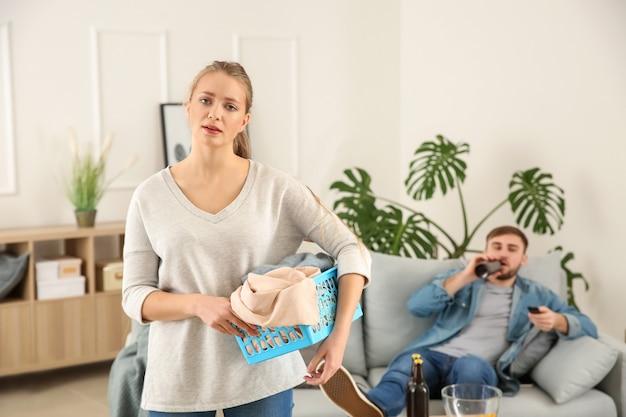 Smutna gospodyni domowa z praniem i jej leniwy mąż odpoczywa na kanapie