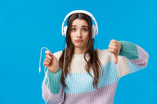 Smutna i niezadowolona, ponura urocza brunetka w dużych słuchawkach, krzywiąca się rozczarowana, pokazująca kciuk w dół i trzymająca upuszczony drut słuchawek, stojąca na niebiesko
