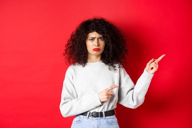 Smutna i ponura brunetka z kręconymi włosami, marszcząca brwi i wyglądająca na rozczarowaną, wskazująca palcami w prawo w logo, stojąca na czerwonej ścianie