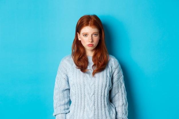 Smutna i ponura ruda nastolatka wpatrująca się w kamerę niespokojna, czująca się źle, stojąca na tle niebieskiego backgorunda w swetrze.