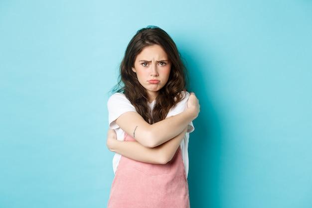 Smutna i posępna młoda kobieta nadyma się, pociesza się przytulaniem, przytula ciało i wygląda na zdenerwowaną z powodu czegoś niesprawiedliwego, stojąc na niebieskim tle.