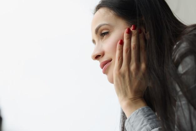 Smutna i przygnębiona kobieta wygląda przez okno