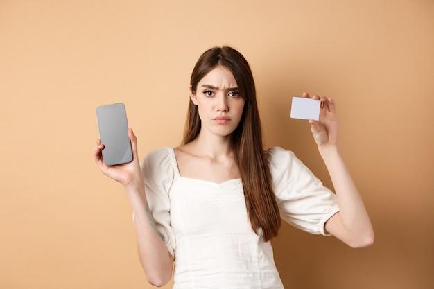 Smutna i rozczarowana dziewczyna pokazująca pusty ekran smartfona i plastikową kartę kredytową, narzekająca i marszcząca brwi, stojąca na beżowym tle.