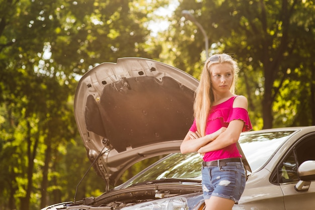 Smutna i zła kobieta z uszkodzonego samochodu