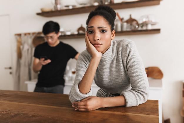 Smutna kobieta afroamerykanów, opierając się pod ręką w zamyśleniu
