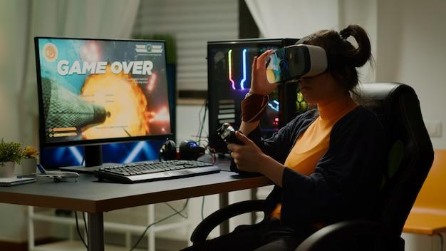 Smutna kobieta grająca w zestaw słuchawkowy wirtualnej rzeczywistości przegrywająca kosmiczne strzelanki na turnieju online za pomocą bezprzewodowego kontrolera. pokonany gracz grający o rozgrywkę online późną nocą w pokoju gier