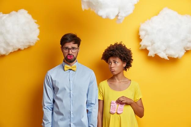 Smutna kobieta i mężczyzna oczekują dziecka, dowiadują się o złych wiadomościach, pozują ze skarpetkami sutkowymi i dziecięcymi, przygotowują się do zostania rodzicami, stają obok siebie na żółto. młoda rodzina przygotowuje się do porodu