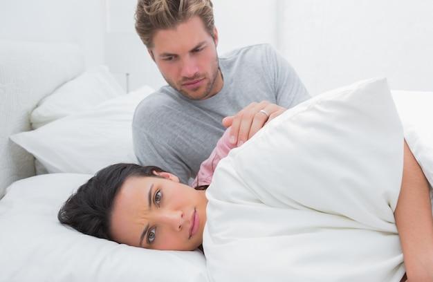 Smutna kobieta ignoruje jej partnera w jej łóżku