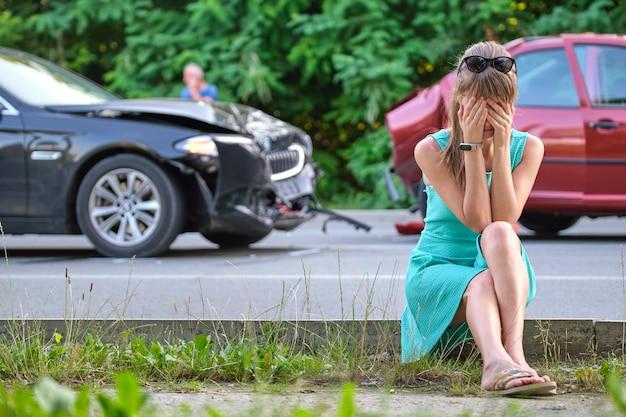Smutna kobieta-kierowca siedząca na ulicy w szoku po wypadku samochodowym. koncepcja bezpieczeństwa drogowego i ubezpieczenia pojazdu.