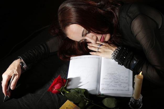 Smutna kobieta leży na stole oświetlonym świecą leży róża