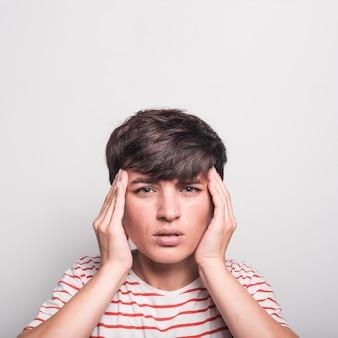 Smutna kobieta ma migrenę przeciw białemu tłu