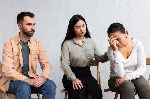 Smutna kobieta na sesji terapii grupowej opowiada o swoich problemach