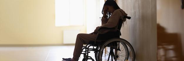 Smutna kobieta niepełnosprawna siedząca na wózku inwalidzkim i trzymająca głowę w klinice