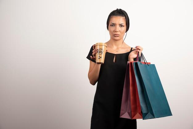 Smutna kobieta niosąca torby na zakupy i kawę na białej ścianie.