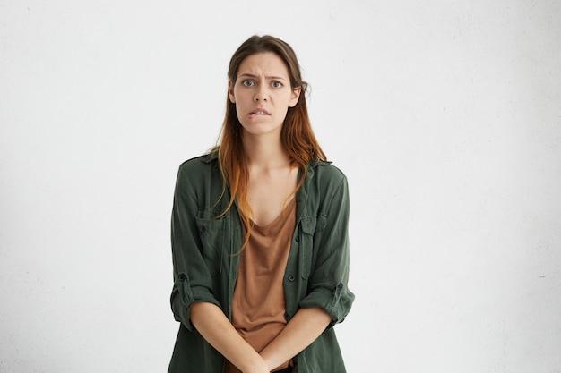 Smutna kobieta o prostych włosach, ciemnobrązowych oczach przygryzających dolną wargę. zdziwiona kaukaska kobieta próbująca znaleźć wyjście w trudnej sytuacji. uczucia i emocje