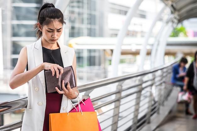 Smutna kobieta patrzeje jej portfel