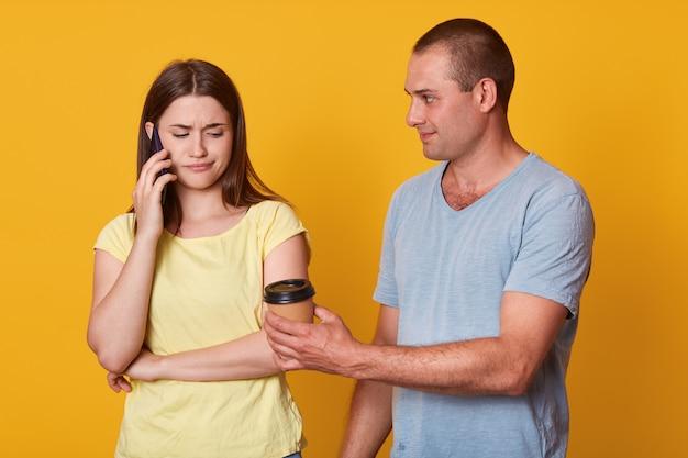 Smutna kobieta patrzy w dół ze zdenerwowanym wyrazem twarzy, rozmawiając przez inteligentny telefon