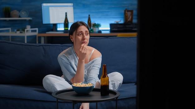 Smutna kobieta płacze oglądając dramat w telewizji, siedząc na kanapie i jedząc popcorn