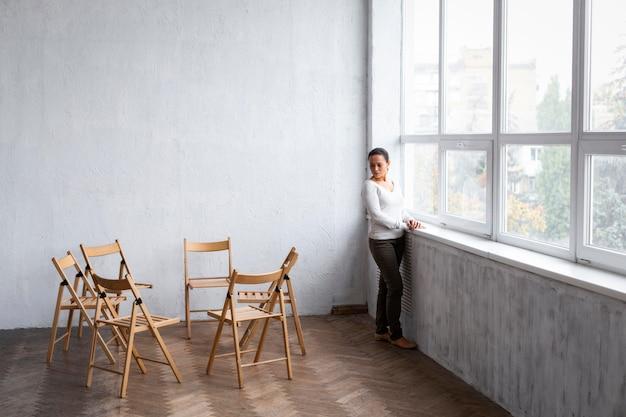 Smutna kobieta przy parapecie na sesji terapii grupowej z pustymi krzesłami