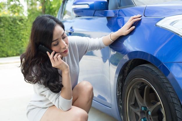 Smutna kobieta siedząca przy samochodzie martwi się o opony i rozmawia przez telefon z mechanikiem samochodowym