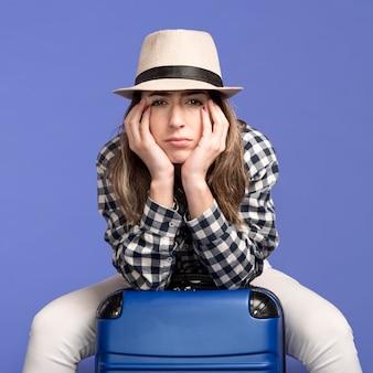 Smutna kobieta siedzi na bagażu