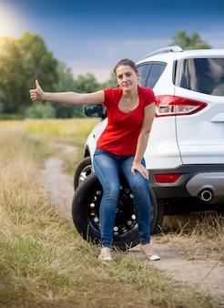 Smutna kobieta siedzi na kole w zepsutym samochodzie w polu i autostopem