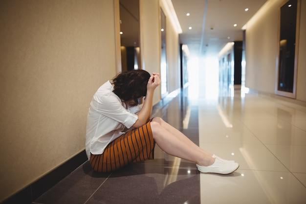 Smutna kobieta siedzi na korytarzu