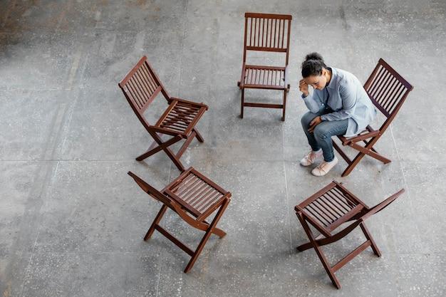 Smutna kobieta siedzi na krześle pełny strzał