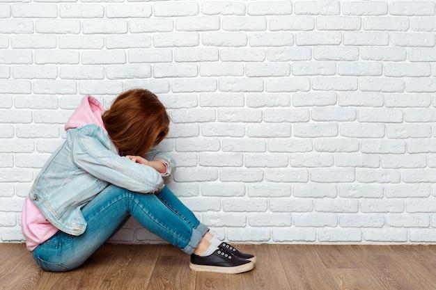 Smutna kobieta siedzi na podłodze w pobliżu ściany
