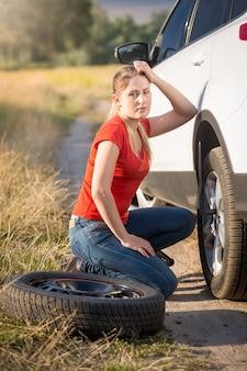 Smutna kobieta siedzi przy zepsutym samochodzie i próbuje zmienić gumę