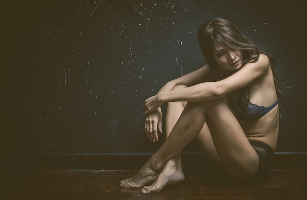 Smutna kobieta siedzi sama w pustym pokoju