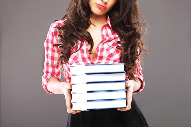 Smutna kobieta stojąca ze stosem książek na szarym tle