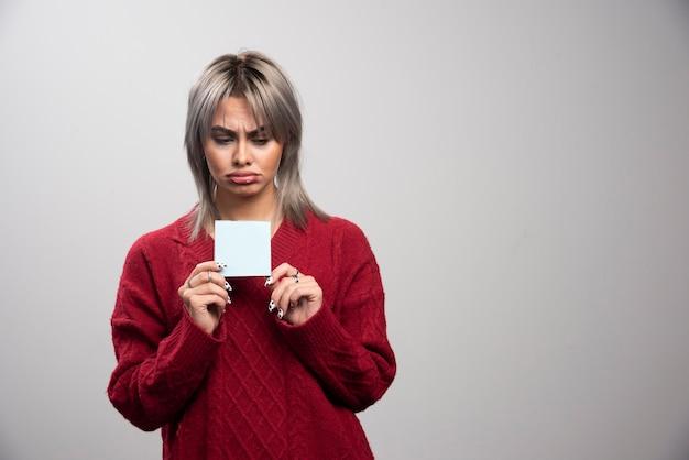 Smutna kobieta trzyma notatnik na szarym tle.