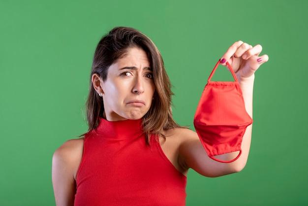 Smutna kobieta trzymając maskę