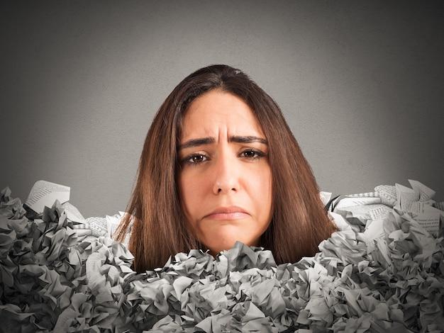 Smutna kobieta uwięziona w górze papierkowej roboty