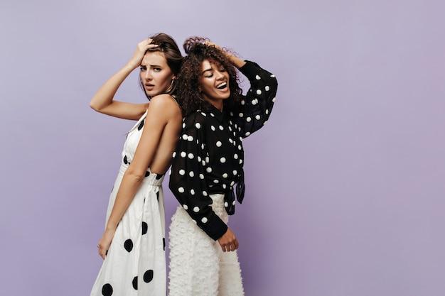 Smutna kobieta w jasnych ubraniach w kropki, patrząc w kamerę i stojąc plecami do wesołego przyjaciela w czarnej koszuli na liliowej ścianie