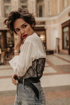 Smutna kobieta w lekkiej bluzce z koronką i dżinsami z paskiem pozuje na ulicy. modna kobieta z krótkimi włosami i czerwoną szminką odwraca wzrok w mieście.