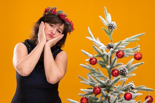 Smutna kobieta w średnim wieku ubrana w świąteczny wieniec na głowę i świecącą girlandę wokół szyi, stojąca w pobliżu ozdobionej choinki