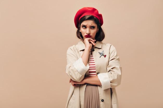 Smutna kobieta w stylowych pozach wykopu i berecie na beżowym tle. zdenerwowana dziewczyna w czerwonym kapeluszu, sweter w paski i płaszcz przeciwdeszczowy, pozowanie na kamery.