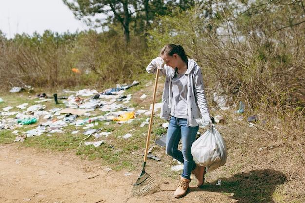 Smutna kobieta w zwykłych ubraniach, sprzątająca, trzymająca worki na śmieci, opierając się na grabie do zbierania śmieci w zaśmieconym parku