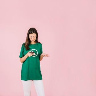 Smutna kobieta wzrusza ramionami przeciw różowemu tłu z smartphone
