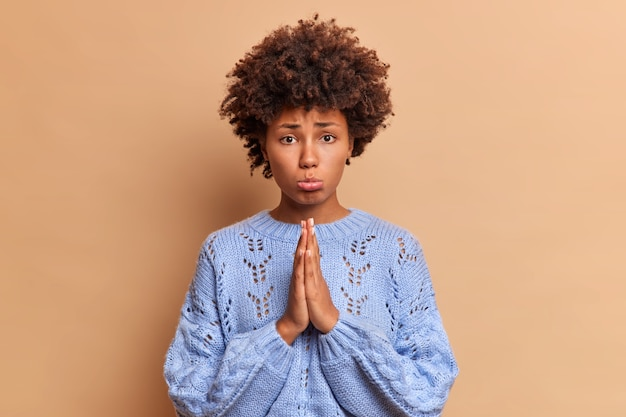 Smutna kobieta z kręconymi włosami zaciska usta i trzyma dłonie razem i wygląda nieszczęśliwie błagając z przodu, prosi o przeprosiny, potrzebuje pomocy, pozuje na brązowej ścianie, czuje się winna, że zrobiła coś złego