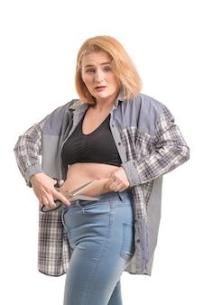 Smutna kobieta z nadwagą z nożyczkami na białym tle. koncepcja utraty wagi