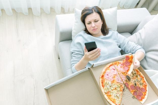 Smutna kobiety łasowania pizza i mienie telefon kłaść na kanapie w domu, błękitny brzmienie