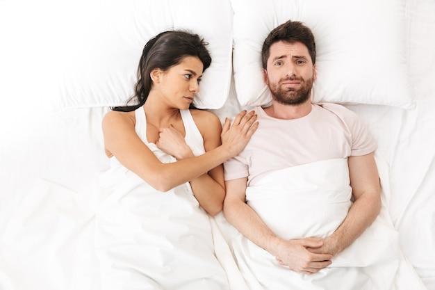 Smutna, kochająca się para leży w łóżku pod kocem i rozmawia ze sobą