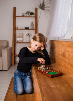 Smutna mała blondynka siedzi i gra w szachy w pokoju