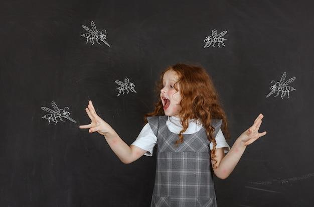 Smutna mała dziewczynka boi się gryzących komarów latających wokół niej.