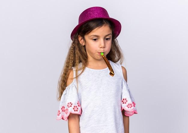 Smutna mała kaukaska dziewczyna w fioletowym kapeluszu imprezowym dmuchający gwizdek na białej ścianie z miejscem na kopię