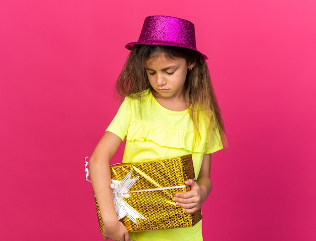 Smutna mała kaukaska dziewczyna w fioletowym kapeluszu imprezowym trzymająca pudełko na prezent na różowej ścianie z miejscem na kopię